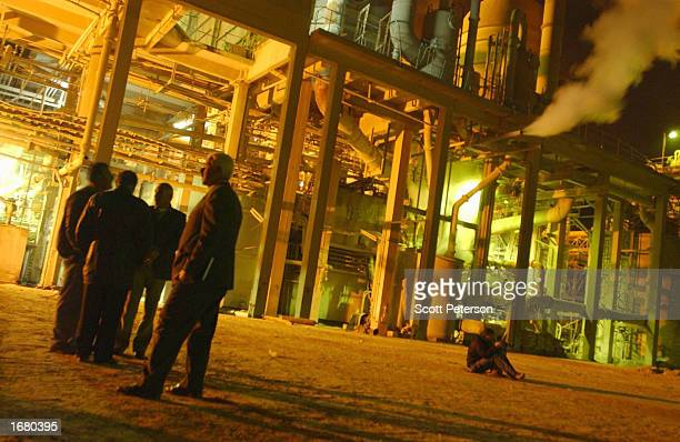 Iraqi officials stand in front of a phosphate factory December 10 2002 near Iraq's border with Syria at Qaim Ukashat UN atomic weapons inspectors...