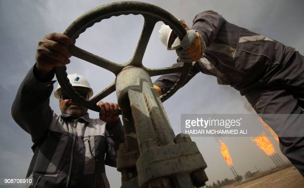 Iraqi oil technicians turn a valve at a gas installation as flames resulting from the burning of excess hydrocarbons rise in the background at the...