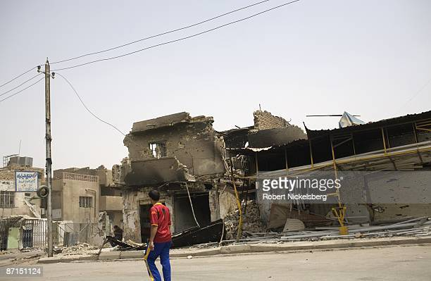 Iraqi pedestrians walk past destroyed buildings after two months of fighting along front line Al Quds Street in Sadr City the 25 million Shia...