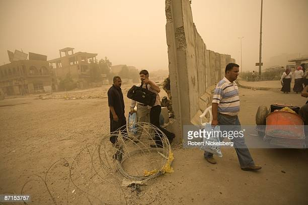 Iraqi pedestrians walk through an opening in the concrete barrier along Al Quds and Fallah Streets in Sadr City the 25 million Shia dominated...