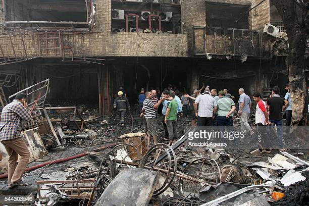 Iraqi people are seen at the site of a suicide car bombing claimed by the terrorist organization DAESH in the Karrada neighborhood of Baghdad Iraq on...