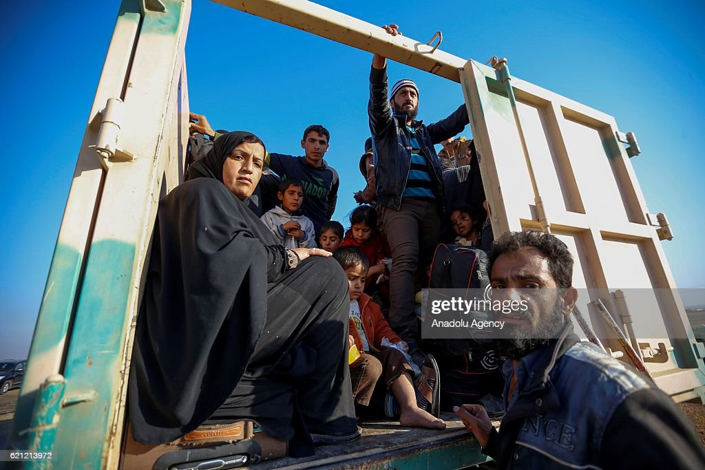 Iraqi people are seen into the vehicle as they wait for security reasons as they fled during clashes between Iraqi army forces and Daesh terrorists at al-Malayin, al-Samah, al-Khazra, Kirkukli, al-Quds and al-Karama districts to safe zones with military vehicles to Khazir refugee camp as the operation to retake Iraq's Mosul from Daesh terrorists continues in Mosul, Iraq on November 5, 2016. A much anticipated Mosul offensive to liberate the city from Daesh began midnight of 16th of October 2016.