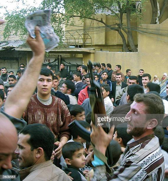 Iraqi people celebrate the capture of ousted dictator Saddam Hussein 14 December 2003 in Baquba 60km northeast of Baghdad Saddam Hussein has been...