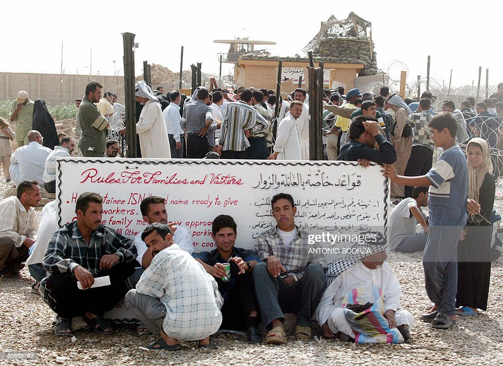 Iraqi people gather at the entrance of the Abu Ghraib prison, 30 kms west of Baghdad, 20 May 2004 in hope of getting information about their loved ones held by US forces at the detention center. US troops faced further embarrassment amid claims they killed dozens of people at a wedding celebration in a remote western Iraqi town, at a time when the occupation forces are already reeling from a prison abuse scandal. AFP PHOTO/Antonio SCORZA