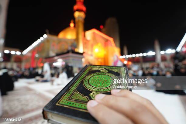 Iraqi people pray as they hold Quran over their heads on the occasion of entering the last 10 days of Ramadan month at Imam Ali Holy Shrine in Najaf,...
