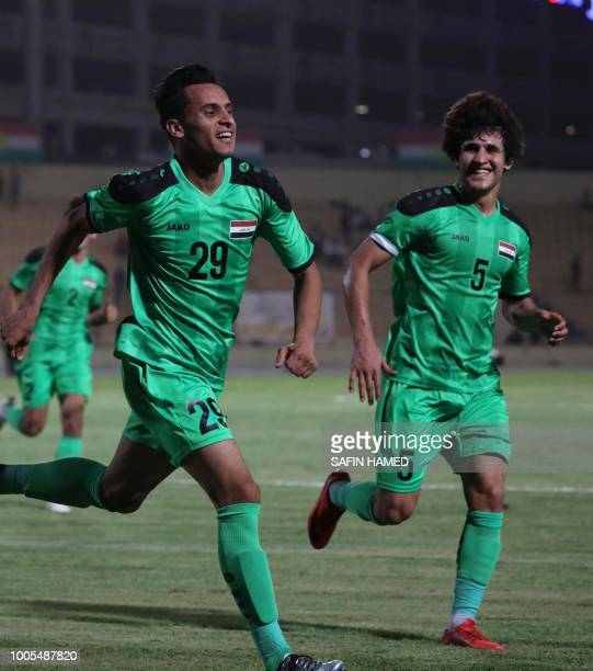 Iraqi player Ahmed Jalal celebrates with teammate Safa Hadi after scoring a goal against Iran during their U23 friendly match in Arbil the capital of...