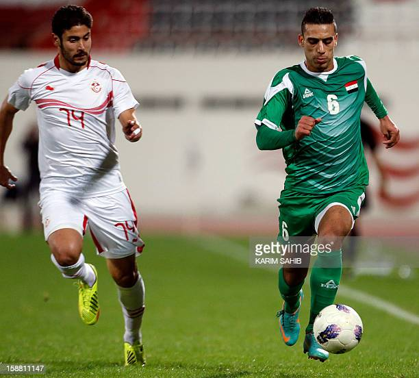 Iraqi player Ali Adnan vies for the ball against Tunisian Majdi Tarawi during their friendly football match in the UAE emirate of Sharjah on December...