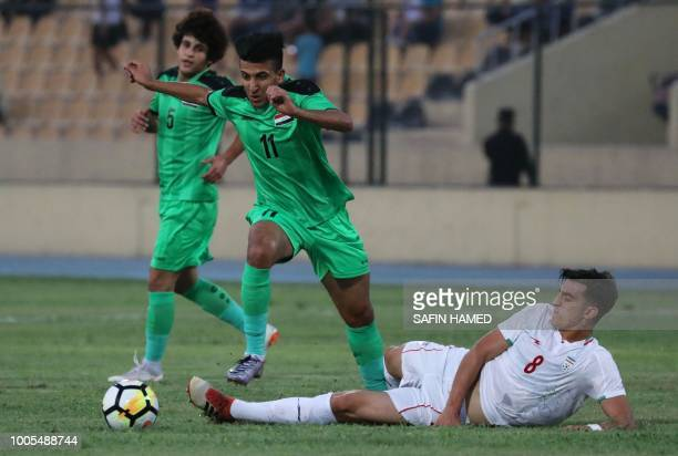 Iraqi player Amjed Atwan challenges Iranian player Mohammed Soltani as Iraqi player Safa Hadi watches during U23 friendly match at the Francois...