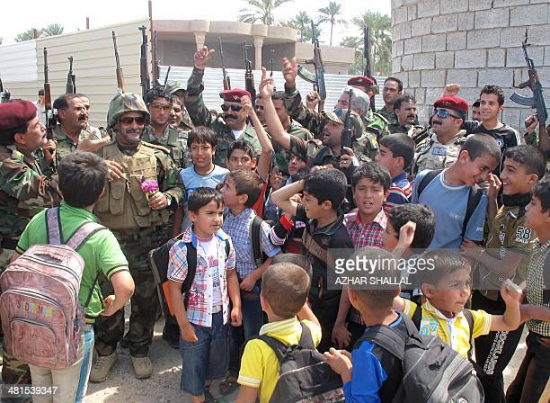 Iraqi police and soldiers cheer with school children as they parade in the city of Ramadi the capital of Iraq's Anbar province west of Baghdad on...