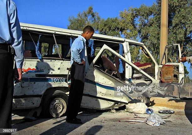 Iraqi police check the wreckage of a mini bus that was hit by a roadside bomb in the restive city of Baqubah 60 kms northeast of Baghdad 03 November...