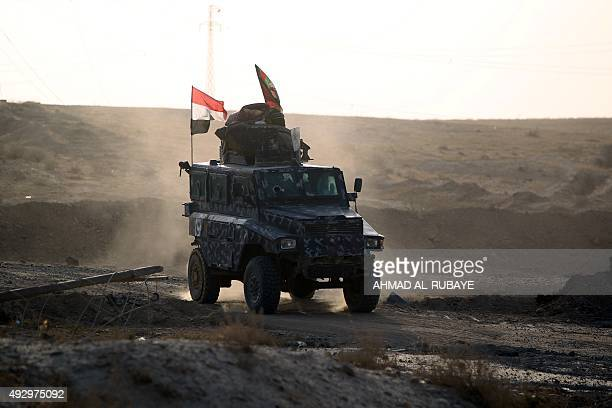 Iraqi police fighting alongside Iraqi forces and Popular Mobilisation units drive their vehicle in the town of Baiji north of Tikrit during fighting...