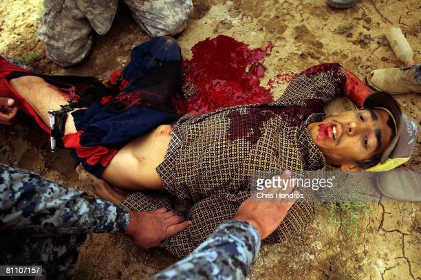 Iraqi police forces and US troops of the 2nd Battalion 30th Infantry Regiment of the 10th Mountain Division surround and treat a wounded Iraqi man...