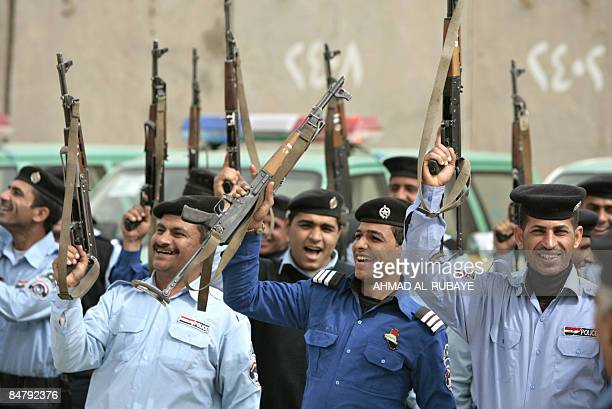 Iraqi police hold up their weapons as they celebrate following the transfer by US Comanche troops 5th Squadron 4th Cavalry regiment of the JSS Ghaz...