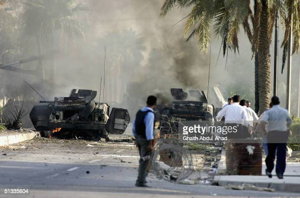Iraqi police officers rush torards two wrecked humvees belonging to the 1st Marine Expeditionary Force are seen September 22 2004 in the Mansour...