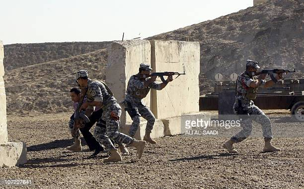 Iraqi police officers under the supervision of NATO run with their rifles during a training session at a military base in Baghdad's airport on...