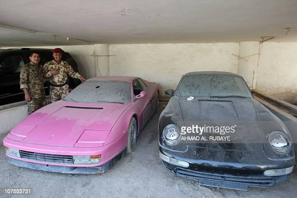 Iraqi police pose next to a pink Ferrari Testarossa and a black Porshe which belonged to Uday Hussein son of hanged leader Saddam Hussein at police...