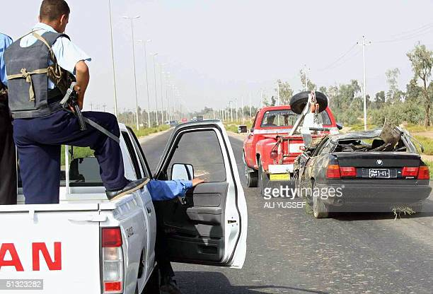 Iraqi police secure the area as a wrecker pulls a damaged car part of the convoy of Hashin Shehada a senior Diyala provincial official 19 September...