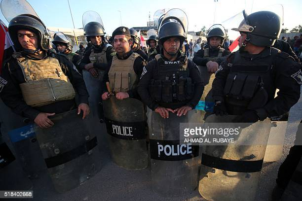 Iraqi police stand guard as supporters of Iraqi Shiite cleric Moqtada alSadr protest outside the heavily fortified Green Zone in Baghdad on March 31...
