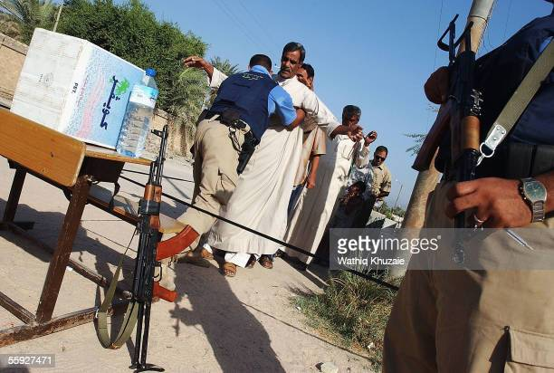 Iraqi policeman search Iraqi voters before they enter a polling station on October 15, 2005 in the city of Basra, 340 miles south of Baghdad, Iraq....