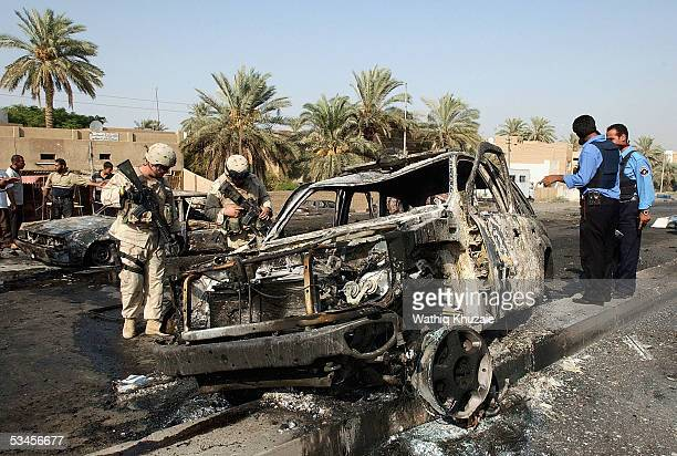 Iraqi policemen and US soldiers secure the scene of a car bomb explosion on August 24 2005 in the Hay alJamma district western Baghdad Iraq A car...