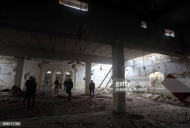 Iraqi policemen check the damage at a Sunni mosque that was destroyed during violence earlier in the month in the town of Muqdadiyah northeast of...
