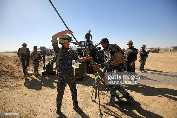 TOPSHOT Iraqi policemen clean a weapon at the Qayyarah military base about 60 kilometres south of Mosul on October 16 as they prepare for an...