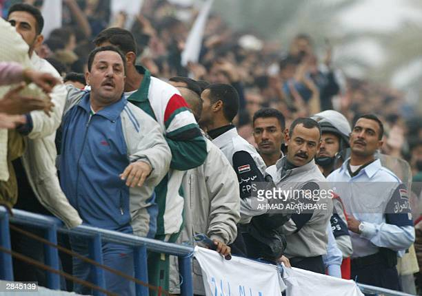 Iraqi policemen guard the crowd during the final between rival Baghdad clubs alZawra and alTalaba of the Baghdad Cup the first national soccer...