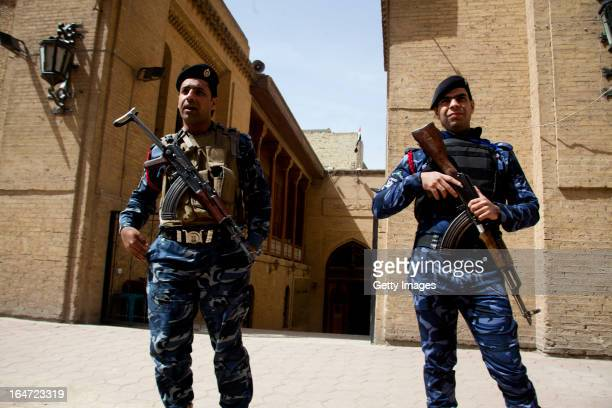 Iraqi policemen guard the entrance to the Baghdad Folklore Museum March 18 2013 in Baghdad Iraq Ten years after the regime of Saddam Hussein was...