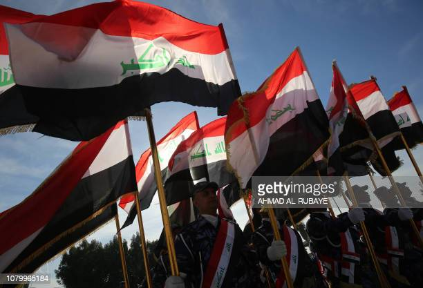 TOPSHOT Iraqi policemen hold their national flag and march during a parade in Baghdad on January 10 2019 to mark the graduation of 158 Iraqi...