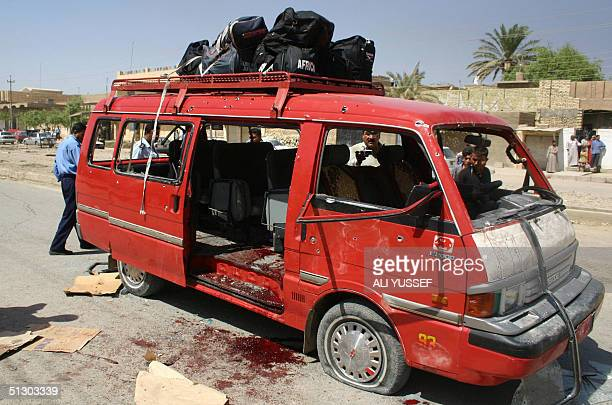 Iraqi policemen inspect a minibus that was attacked 14 September in Baquba northeast of Baghdad Twelve Iraqi policemen and their driver were killed...
