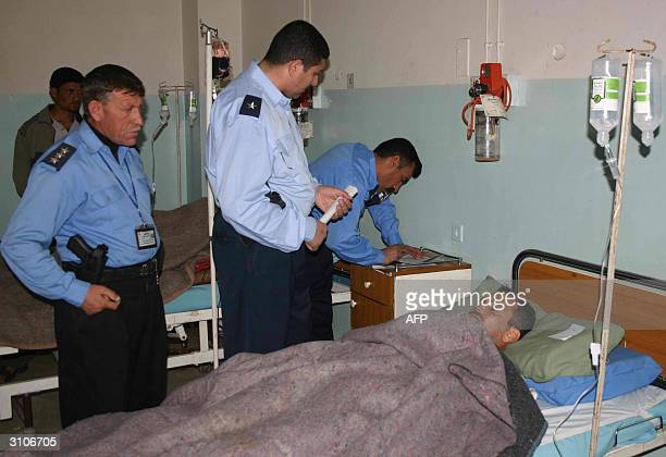 Iraqi policemen interrogate one of 10 people wounded in a shooting attack in which three others were killed in Baquba 60 kms northeast of Baghdad 18...