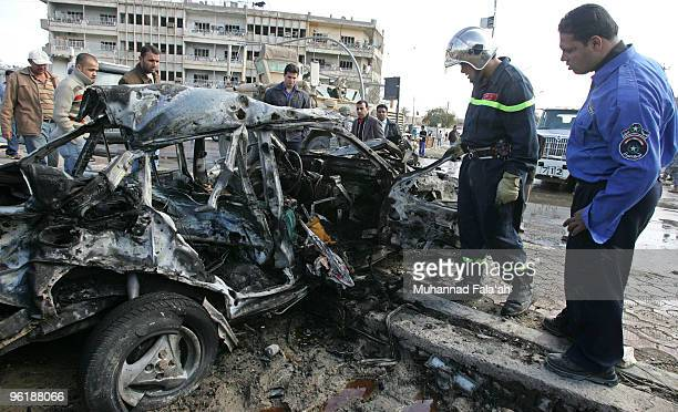Iraqi policemen investigate a car damaged by a suicide car bomb explosion near an Interior Ministry police forensics office on January 26 2010 in...