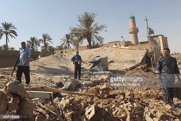 Iraqi policemen make their way on the rubble of a building targeted earlier this month by a jihadist attack in the town of Dhuluiyah north of Baghdad...