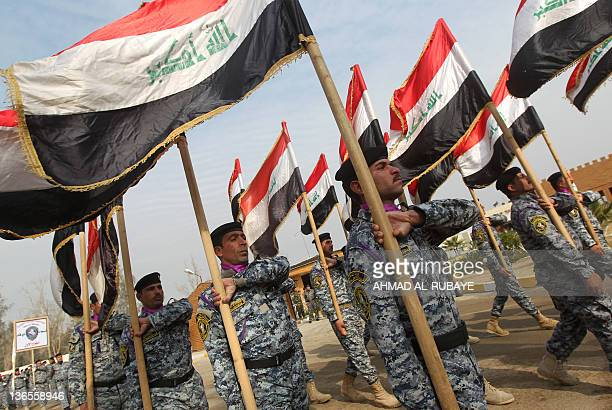 Iraqi policemen march holding their national flags during the first graduation ceremony for 440 national policemen trained solely by the Iraqi...