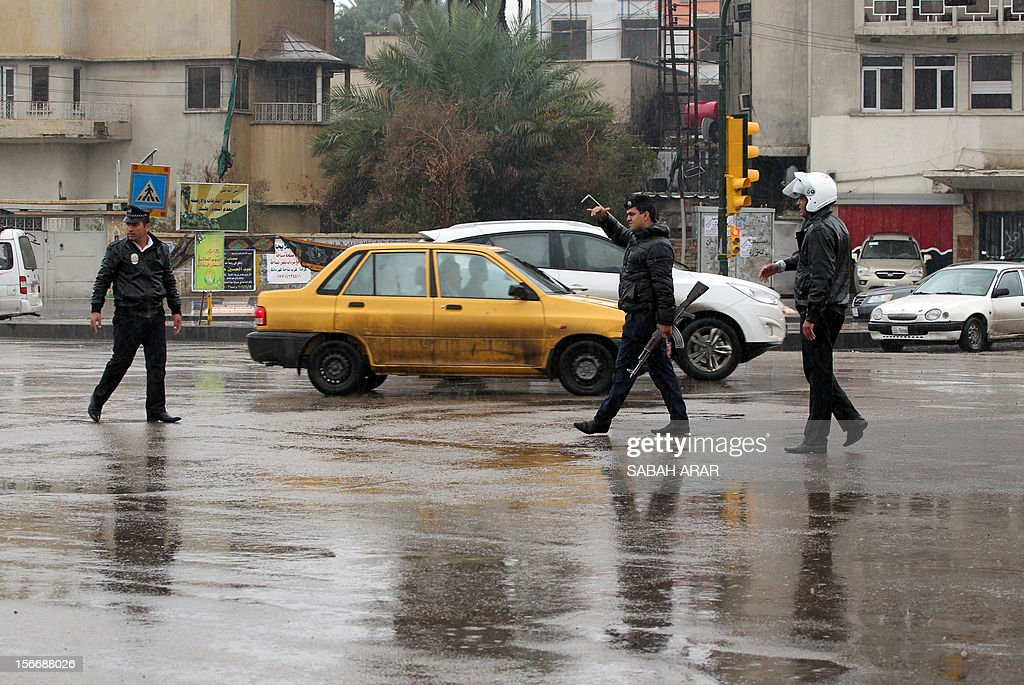 Iraqi policemen monitor a junction after continuous overnight rainfall inundated many of Baghdad's main streets on November 19, 2012, causing problems with the capitals sewage system.