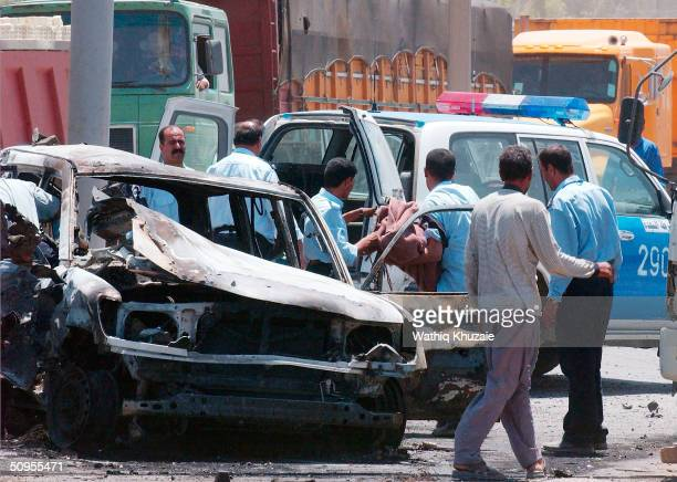 Iraqi policemen remove a body from the scene of a car bomb attack in which at least 12 people were killed, among them 4 Iraqi policemen, on June 13,...