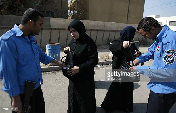 Iraqi policemen search the bags of two Iraqi women at the entrance to a Baghdad hospital following a suicide bomb attack in Baghdad's central Karrada...