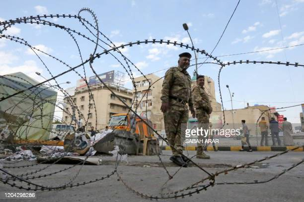 Iraqi policemen stand behind barbered wire during ongoing antigovernment demonstrations in Baghdad's Tahrir Square on March 1 2020 Iraq's bitterly...