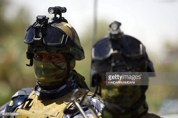 Iraqi policemen stand guard on a street in the central Shiite Muslim shrine city of Najaf on June 14 2014 as security forces ready a counteroffensive...