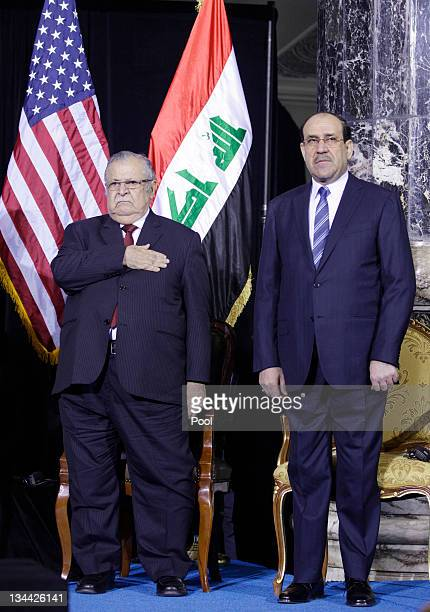 Iraqi President Jalal Talabani and Iraqi Prime Minister Nouri alMaliki stand during the playing of the Iraqi and US National Anthems at a special...