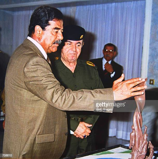 Iraqi President Saddam Hussein examines a model for a monument proposal for AlNasr bridge in Nassyria province April 22 2002 in Baghdad Iraq The...