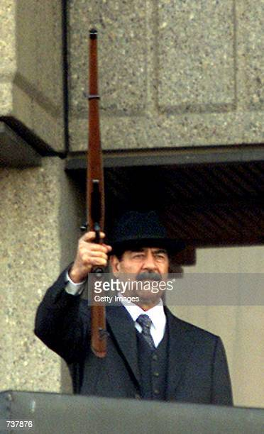 Iraqi President Saddam Hussein fires shots into the air December 31 2000 Iraq dismissed reports on January 3 2001 that Hussein had suffered a stroke...