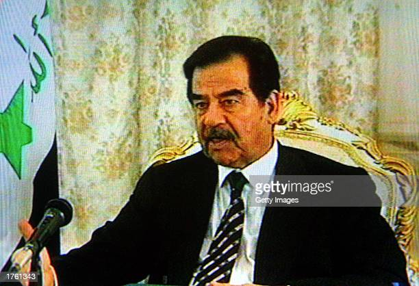 Iraqi President Saddam Hussein is shown being interviewed by veteran labour politican Tony Benn in a television image February 4 2003 in Baghdad Iraq...