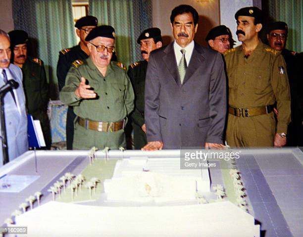 Iraqi president Saddam Hussein listens to Deputy Prime Minister Tariq Aziz as they look at a model of the al Amiria shelter September 3 2001 in...