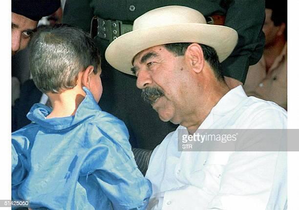 Iraqi President Saddam Hussein plays with an Iraqi child 16 September in the area of Salahuddin near his birthplace in Tikrit The Iraqi news agency...