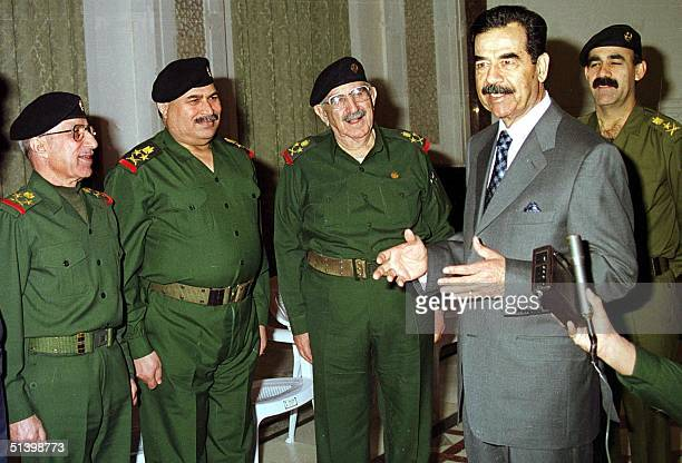 Iraqi President Saddam Hussein talks to members of Iraqi military leadership on the 79th anniversary of Army Day in Baghdad 06 January 2000 Military...
