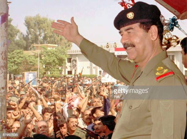 Iraqi President Saddam Hussein waves to his supporters in his first public appearance in Baghdad 18 October since he was reelected as President for...