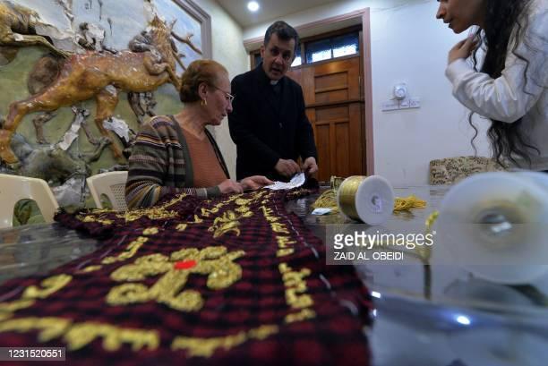 Iraqi priest Ammar Yaqo looks on as Karjiya Baqtar embroiders a precious prayer shawl using golden thread, to gift to Pope Francis during his...