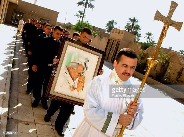 Iraqi Priests walk with a portrait of the Pope on their way to a service for Pope John Paul II on April 2005 at a Catholic church in Baghdad Iraq...