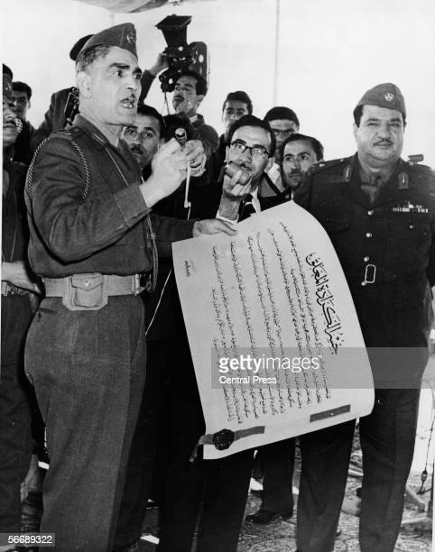 Iraqi Prime Minister and military officer General Abdul Karim Qassim holds a large scroll and delivers a speech for the laying of the foundation...